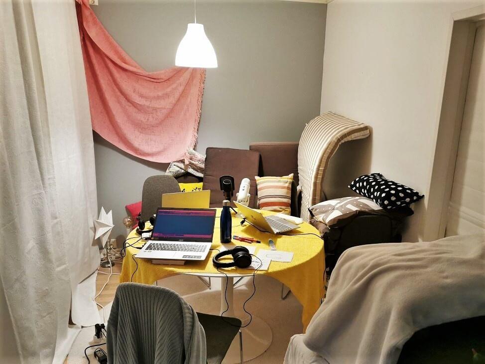 Viltein, tyynyin ja patjoin vuorattu kotistudio verkkovalmennuksen podcastien nauhoittamiseen.